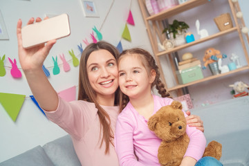 Mother and daughter together at home taking photos on smartphone