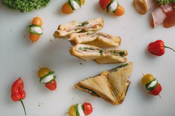 Club sandwich with ham, salami, smoked beef, cheese, lettuce and arugula. Caprese salad on sticks.