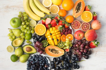 Healthy food background, assortment of fruits in rainbow colours on the off white table arranged in a circle, top view, selective focus