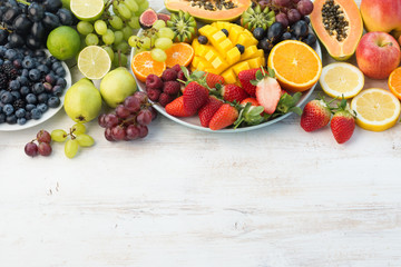 Fresh fruits and vegetables in rainbow colours on the off white table, copy space, selective focus
