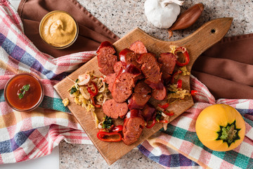 Sliced sausage and mix of fresh vegetables served on a rustic wooden board, mustard, ketchup, fresh hot chili peppers and herbs.