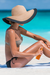 Sexy bikini woman putting suntan lotion oil on tanned skin. Girl tourist applying sunblock cream or mosquito repellent on body holding bottle. Model wearing sun hat.
