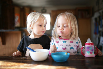 Two Little Toddler Girls Eating Breakfast Together