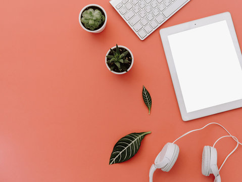 Top view of creative woman's desktop, white tablet and headphones with blank copy space screen. Mock up, flat lay, pink pastel background