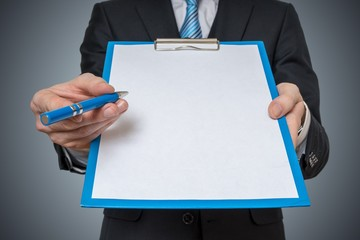 Man is showing and offering blank white paper in clipboard with pen.