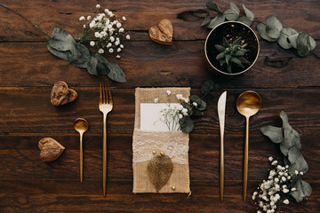 Rustic Wedding. Vintage gold cutlery with eucalyptus an old wooden background.
