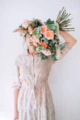 the girl in a gentle dress is standing with her back and holding her bouquet with pink roses and covering her face against the white wall