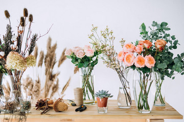 Obraz pink roses on a wooden table on which are located roses, dried flowers cones, greens, scissors, rope, bumps on a white wall background - fototapety do salonu