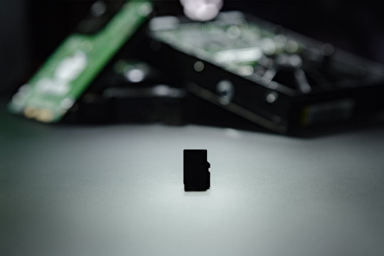 Silhouette of micro SD cards on the background of hard drives as a replacement for old storage methods. Computer and hdd concept.