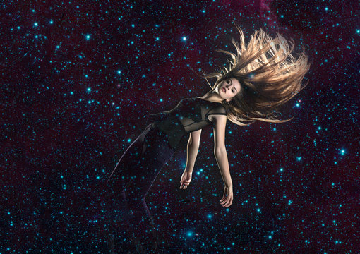 Beautiful, long haired woman falling through stars in space, elements of this image furnished by NASA