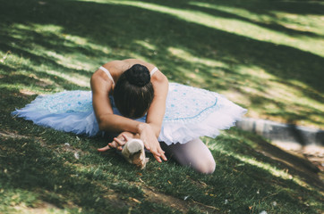 ballerina posing in the park on the grass