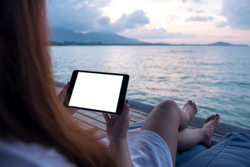 Mockup image of a woman holding and using black tablet with blank white desktop screen while sitting by the sea with blue sky background