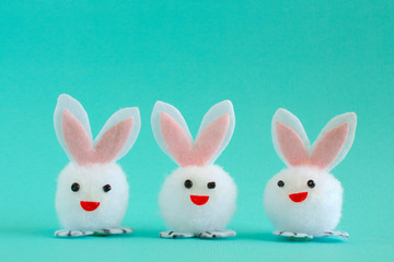 Three fuzzy white pom pom Easter Bunnies with pink ears on an aqua background.