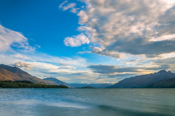Sunset view from Glenorchy wharf with colorful clouds moving against the beautiful mountain range at the northern end of lake Wakatipu in New Zealand, South Island.