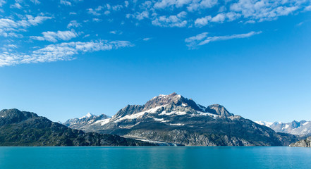 Snow-capped mountain peak in Glacier Bay National Park with sky and clouds