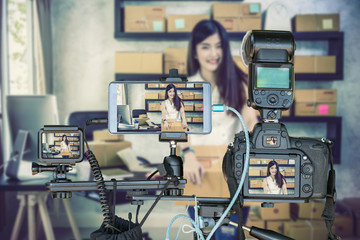 Professional set of camera with smart mobile phone and action camera on tripod over young asian teenager owner business woman work at home for online shopping, Live Streaming for entrepreneur concept