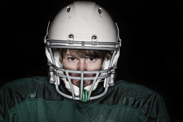 Low key harsh flash image of a boy in a football uniform