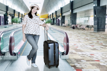 beautiful female tourist wearing with suitcase in an airport