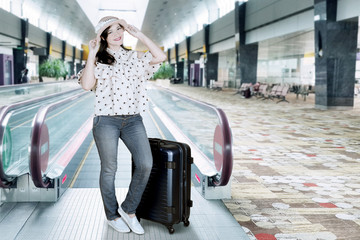 Female tourist wearing hat in an airport