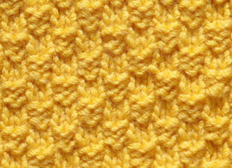 Knitting handmade, a texture of yellow woolen thread. Background with orange patterns, a pattern of knitted fabric for products.