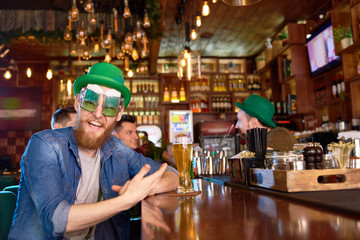 Portrait of joyful red-haired man wearing funny party glasses and green bowler hat looking at camera with toothy smile while sitting at bar counter, group of friends behind him