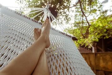 In de dag Ontspanning Crop shot of barefoot feet lying in white hammock and lounging in backyard.