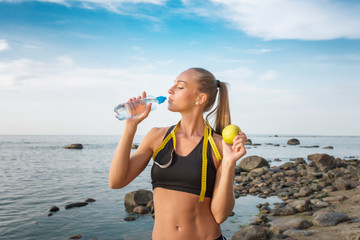 young beautiful sportswoman drinking water on beach with measuring tape
