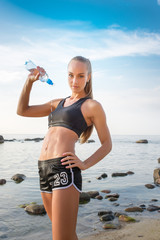 young beautiful sportswoman drinking water on beach