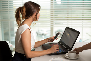 young businesswoman girl with glasses in casual wear sitting at the table carefully look at the documents