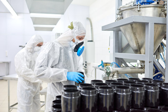 Group of concentrated factory workers wearing coveralls, respirators and rubber gloves filling in plastic bottles with sport supplement
