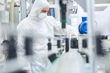 Young man wearing coverall and safety mask working on production line of modern pharmaceutical factory, portrait shot