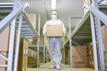 Full length portrait of confident worker wearing safety mask and coverall carrying cardboard box and walking along shelves of pharmaceutical factory warehouse