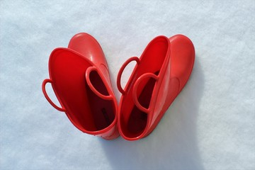 Top view of heart shaped red boots on the snow