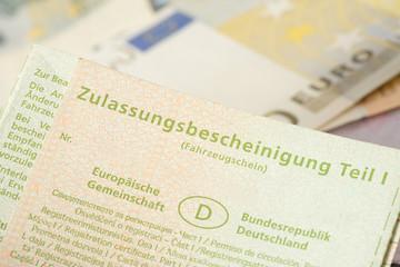 Ein Fahrzeugschein und Euro Geldscheine