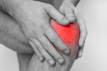 Man with knee pain is holding his aching leg