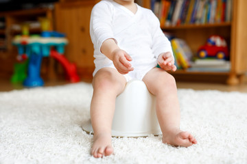 Closeup of legs of cute little 12 months old toddler baby girl child sitting on potty.