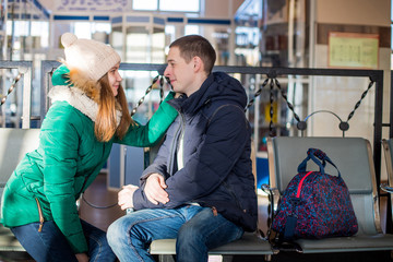Couple in warm clothes in the waiting room at the station