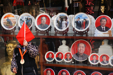 A boy poses for pictures in front of souvenir plates featuring portraits of former and current Chinese leaders including President Xi Jinping and the late Chairman Mao Zedong in Tiananmen Square in Beijing