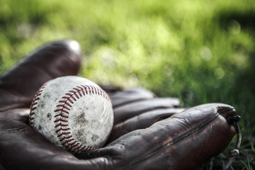Vintage baseball glove and ball on grass. Very shallow depth of focus