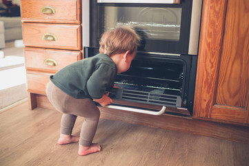 Little toddler exploring oven