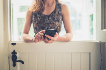 Young woman with phone by stable door