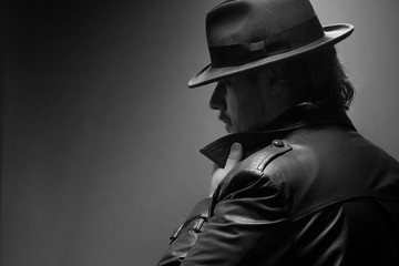 Caucasian Male in vintage trench coat and fedora. Black and white popped collar gaze