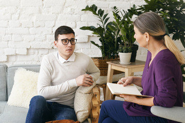 Senior woman psychotherapist or counselor writing something down in notebook during therapy session with frustrated depressed young male in spectacles. Psychology, counseling and mental health