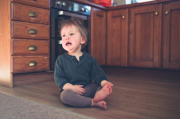 Sad little toddler on kitchen floor