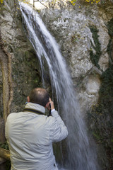 hiker take photo of waterfall