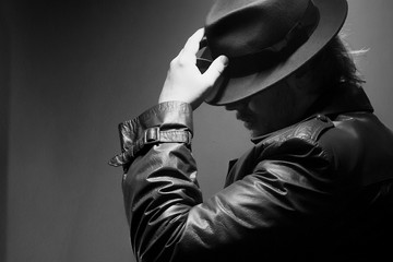 Caucasian Male in vintage trench coat and fedora. Black and white with hand on hat