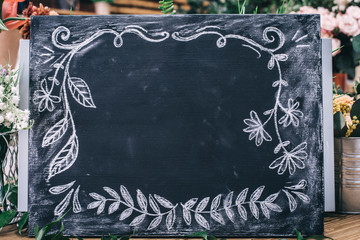 Empty small blackboard with painted ornamental frame and flowers on background.