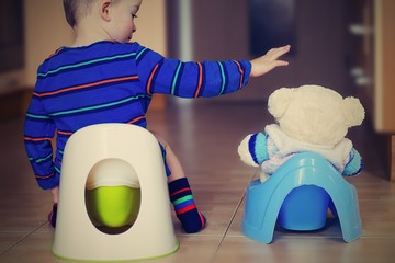 Little boy is training on a potty with his buddy