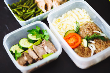 Printed kitchen splashbacks Assortment the healthy food in the containers on black background: snack, dinner, lunch. Baked fish, beans, beef cutlets, mashed potatoes, meat and vegetables tomatoes, cucumbers.