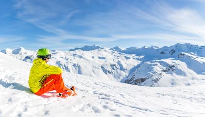 Image of sportive man wearing helmet wearing yellow jacket sitting on snowy slope